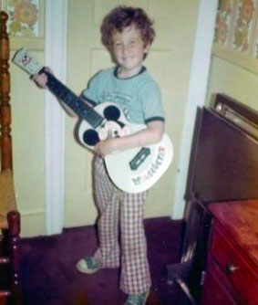 Matt Torrence as a child holding a white guitar